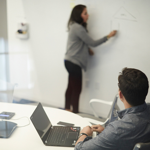 Woman writing on a whiteboard and a man looking at her while sitting at a desk with his laptop open.